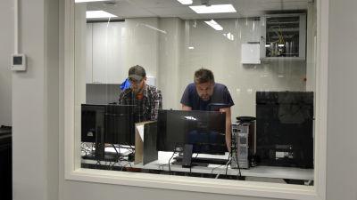 Två män tittar på datorskärmar i ett rum med ett glasfönster.