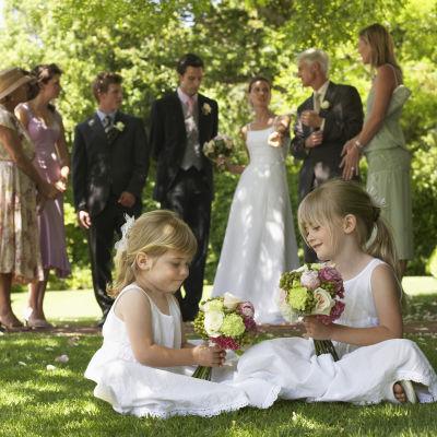 Kaksi pikkutyttöä leikkii kukkakimppujen kanssa, häävieraita taustalla.