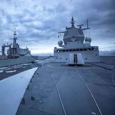 Olycksfartyget, fregatten KNM Helge Ingstad ligger vid sidan om ett militärt tankfartyg