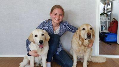 Ung kvinna poserar med sina två hundar.
