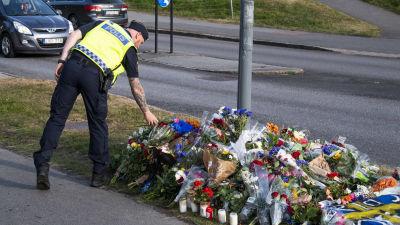 En polis lägger ner blommor vid en lyktstolpe där det samlats blombuketter.