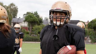 Kvinna med gyllene hjälm och amerikansk fotboll i handen står på en sportplan.