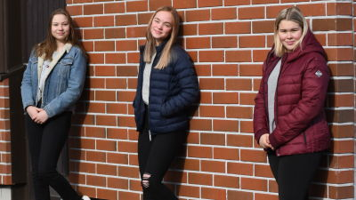 Nea Stolt, Ida Löfgren och Jenny Tarkiainen lutar mot en tegelvägg.