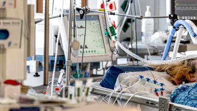 En patient ligger i en sjukhussäng, slangar leder till monitorer på intensivvårdsavdelningen för coronapatienter.