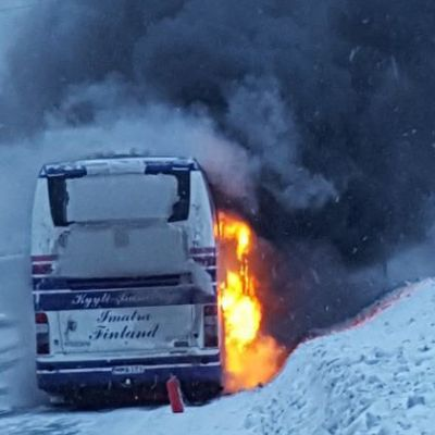 Linja-auto palaa talvella moottoritien varressa.