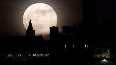 Månens siluett syns mot ett kyrktorn och andra byggnader.