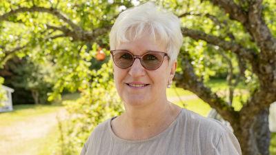 En kvinna står i en trädgård framför ett äppelträd.