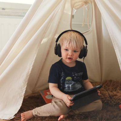 Pieni lapsi kuulokkeet korvilla kuuntelee ohjelmia älylaitteelta.