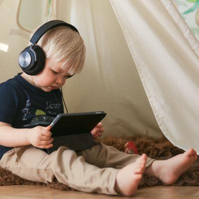 Pieni lapsi kuulokkeet korvilla tutkii älylaitetta.
