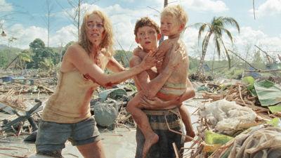 På bilden syns efterspelet av tsunamin i filmen The Impossible. Naomi Watts står intill Tom Holland som håller i ett litet barn i famnen.