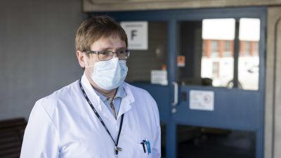 Mansperson i läkarrock och ansiktsmask står utomhus vid sjukhusentré.