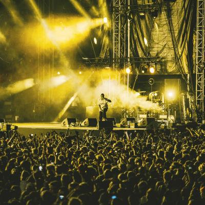 Räppäri Asap Rocky lavalla valtavan yleisömeren edessä Blockfesteillä. Kuva on lavan valojen vuoksi keltainen sävyltään.