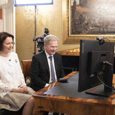 Presidentparen sitter vid en datorskärm och ser glada ut då de samtalar med veteraner.