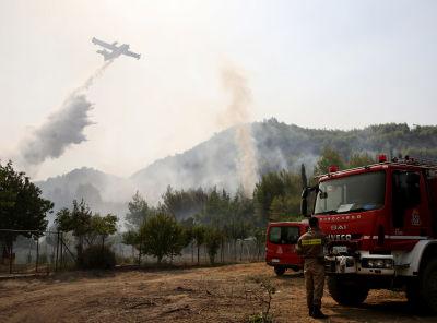Flygplan släcker skogsbrand från luften, brandbil med brandbekämpare i förgrunden. Fotograferat i Koskinas i Grekland.