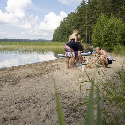 Melomaan lähtenyt perhe rantautuneena hiekkarannalle letunpaistoon trangialla.