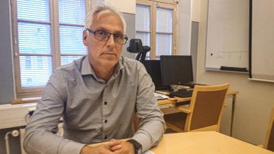 Jan Levander sitter vid ett skrivbord och tittar in i kameran med allvarlig min.