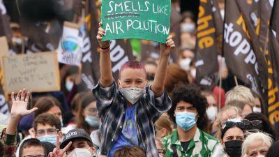 """En ung tysk i flanellskjorta och rödfärgat snaggat hår sitter på sin kompis axlar i ett folkhav under en klimatdemonstration i Berlin. Ungdomen håller uppe en grön skylt med texten """"Smells like air pollution""""."""