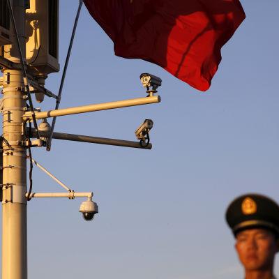 En kinesiska soldat står bredvid en rad övervakningskameror på Himmelska fridens torg i Peking