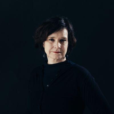 Överkroppen av en kvinna mot svart bakgrund.