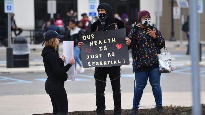 """Tre Amazonanställda demonstrerar mot bolaget. En bär på en skylt med texten """"vår hälsa är lika viktig!"""""""