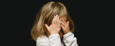 Ett barn håller händerna för ögonen och står framör en helsvart bakgrund.