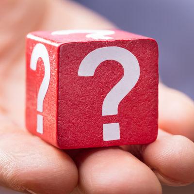 En hand håller i en kub som har flera frågetecken på sig.