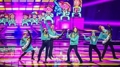 Sex människor med turkosa tröjor på scen