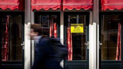 En cyklist passerar i hög fart fönstret på en bordell i stadsdelen De Wallen. Under den partiella nedstängningen i Nederländerna får prostitution inte förekomma.