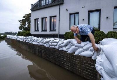 Mies asettelee hiekkasäkkejä kanavan reunalle talon pihalla.