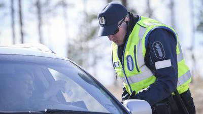 En polis kontrollerar körkortsuppgifter hos en person i en personbil.