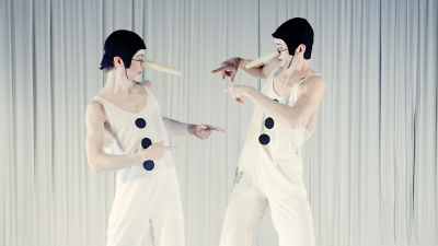 Jakob tillsammans med en annan skådespelare på scen. De är vitt sminkade i ansiktet, vita kläder och en lång lösnäsa fastspänt över huvudet.