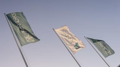 Tre flaggor med texten Åland post vajar i vinden mot en klar himmel.