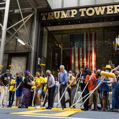 New Yorkin pormestari ja joukko mustia aktivisteja maalaavat keltaista black lives matter -tekstiä kadun pintaan Trump Towerin edessä New Yorkissa.