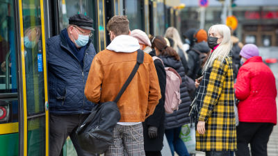 Ihmisiä raitiovaunupysäkillä. 7.4.2021