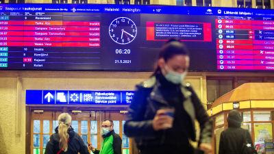 Människor på järnvägsstationen i Helsingfors. I bakgrunden syns ljustavlan med många inställda tåg.
