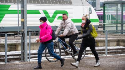 Två kvinnor i munskydd promenerar och en man utan munskydd på cykel på Helsingfors järnvägsstation 25.3.2021