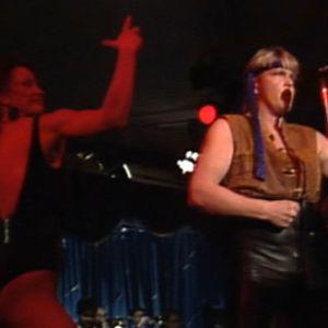 Jokke Seppälä laulaa Rambo-asussa ja vieressä tanssii vähäpukeinen nainen