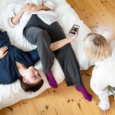 Kolme nuorta naista katselevat puhelimesta Yle Areenaa kimppakämpän olohuoneessa.
