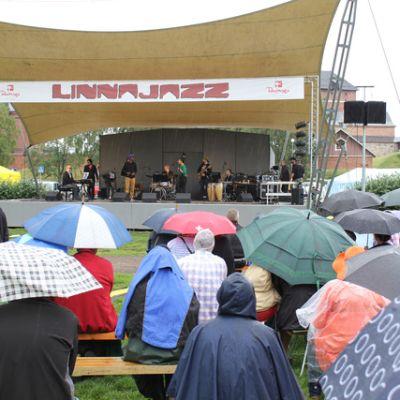 Yleisö kyyristelee sadetta linnanpuiston penkeillä