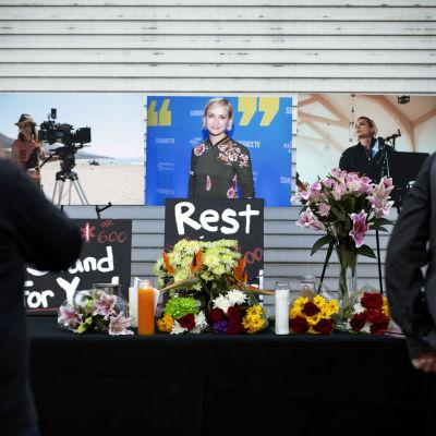 Blommor och ljus står på ett bord framför ett foto på en kvinna.