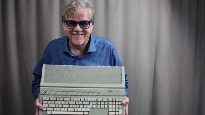 Mikko Alatalo hymyilee kameralle ja esittelee Atarin näppäimistöä.
