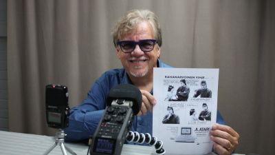 Mikko Alatalo studiossa. Esittelee vanhaa Atari -mainosta, jossa esiintyy poikansa kanssa.