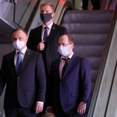 Den sittande presidenten Andrzej Duda (till vänster) och hans medhjälpare bar ansiktsmask då de lämnade en tv-studio efter en valdebatt på onsdagen.