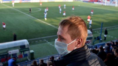 En man med ansiktsmask på en fotbollsplans läktare