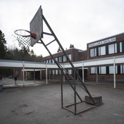 """En skolbyggnad i rött tegel, med en korgbollsställning i förgrunden. På väggen står det """"Winellska skolan""""."""