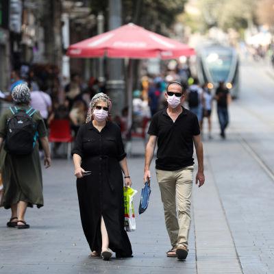 Människor med ansiktsskydd som promenerar på en gata i Jerusalem.