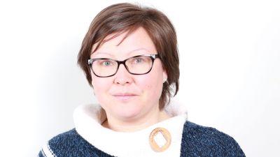 En kvinna i kort mörkt hår och glasögon tittar in i kameran.