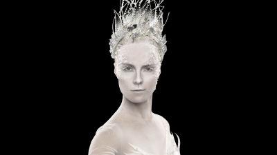 En kvinna med vitt smink med en krona på huvudet.