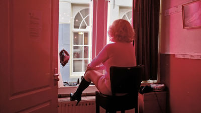 En prostituerad sitter i sitt fönster vid Red light district i Amsterdam