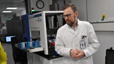 Överläkare Antti Hakanen presenterar apparatur för coronatest.